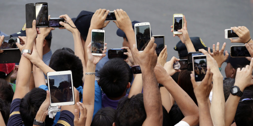 In this Friday, Jan. 16, 2015, photo, Filipino Catholics prepare to take photos, using their mobile phones and tablets, of Pope Francis aboard his Popemobile in Manila, Philippines. Pope Francis is here on a five-day apostolic visit in this predominantly Catholic nation in Asia. (AP Photo/Bullit Marquez)